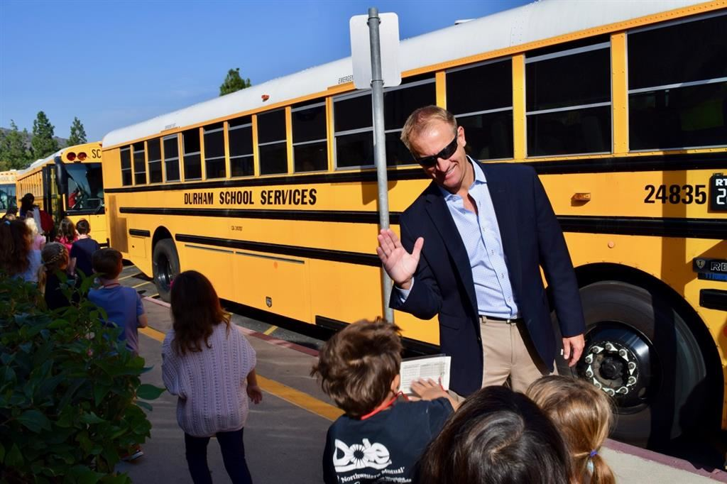 Dr. Stepenosky high-fives students getting on a bus