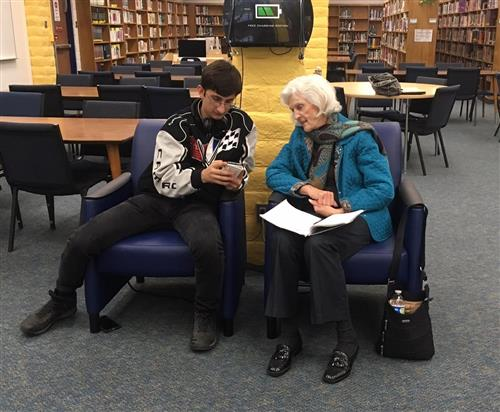 student helps senior with smartphone